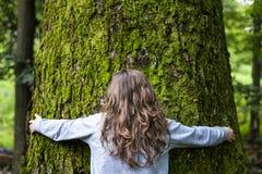 Ung flicka som kramar ett stort träd i skogen Fotografering för Bildbyråer