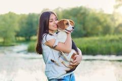 Ung flicka som kramar hennes hund i parkera Royaltyfri Bild