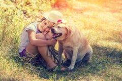 Ung flicka som kramar hunden i skogen arkivfoton