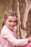 Ung flicka som kramar trädet i skog arkivbilder