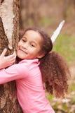 Ung flicka som kramar trädet i skog arkivfoto
