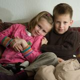 Ung flicka som kudling med hennes äldre broder royaltyfri bild