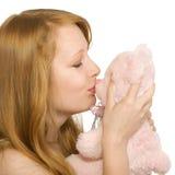 Ung flicka som kysser en nallebjörn som isoleras Arkivfoto