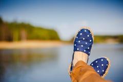 Ung flicka som lägger nära sjön och vila Arkivfoto