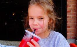Ung flicka som läppjar en kall sommardrink royaltyfria bilder