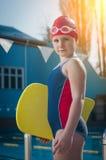 Ung flicka som lär att simma i pölen med ett skumbräde Arkivbild