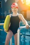 Ung flicka som lär att simma i pölen med ett skumbräde Arkivfoto