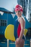 Ung flicka som lär att simma i pölen med skumbrädet Royaltyfri Bild
