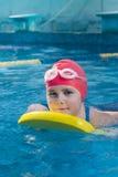 Ung flicka som lär att simma i pölen med skumbrädet Fotografering för Bildbyråer