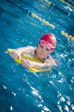Ung flicka som lär att simma i pölen med skumbrädet Royaltyfria Bilder