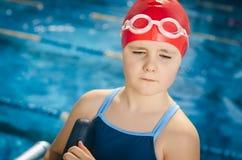 Ung flicka som lär att simma i pölen med skumbrädet Arkivfoton