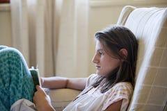 Ung flicka som läser boken Fotografering för Bildbyråer