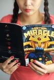 Ung flicka som läser DC-humorboken royaltyfri bild