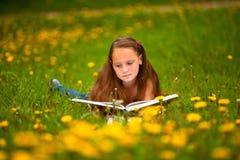 Ung flicka som läser en bok Fotografering för Bildbyråer