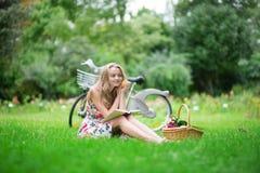 Ung flicka som läser en bok i bygden Fotografering för Bildbyråer