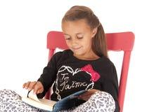 Ung flicka som läser en bok i en röd gungstol Arkivbilder