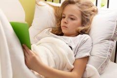 Ung flicka som läser en bok i säng, grunt djup Royaltyfri Fotografi