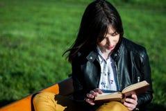 Ung flicka som läser en bok på en solig dag för vår på en bänk i natur arkivbilder