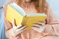 Ung flicka som läser en gammal bok Arkivfoto