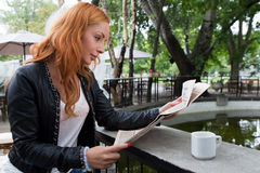 Ung flicka som läser en tidning i kafeteria Arkivbild
