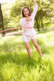 Ung flicka som leker med det Hula beslag i fält Royaltyfria Foton