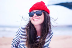 Ung flicka som ler i ett rött lock Royaltyfri Bild