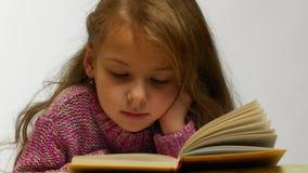 Ung flicka som ler medan läsebok Främre sikt av gulligt tonårigt ligga med den öppnade boken stock video
