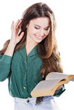 Ung flicka som ler, medan rymma en bok på isolaten Fotografering för Bildbyråer