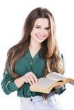 Ung flicka som ler, medan rymma en bok på isolaten Royaltyfri Foto