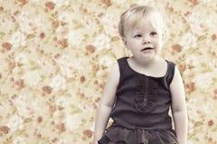 Ung flicka som ler mot blom- bakgrund Royaltyfria Bilder