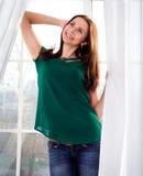 Ung flicka som ler på bakgrunden av ett fönster Arkivfoto