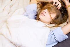 Ung flicka som ligger i hennes säng med smutsigt hår som täcker hennes framsida Arkivbild