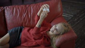 Ung flicka som ligger på den röda soffan och tar selfie stock video