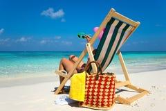 Ung flicka som ligger på en stranddagdrivare med exponeringsglas i hand på royaltyfria foton