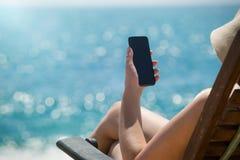 Ung flicka som ligger på en stranddagdrivare med mobiltelefonen i hand på Arkivfoton