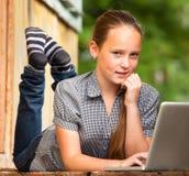 Ung flicka som ligger på farstubron av det lantliga huset med en bärbar dator. Arkivfoton
