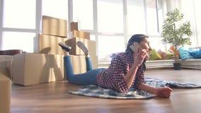Ung flicka som ligger på golvet och talar på telefonen lager videofilmer
