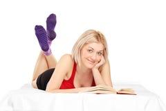 Ung flicka som ligger på säng och läsning en bok Fotografering för Bildbyråer