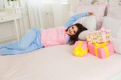 Ung flicka som ligger på sängen Fotografering för Bildbyråer