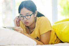 Ung flicka som ligger på sängen och lyssnar till musik Fotografering för Bildbyråer