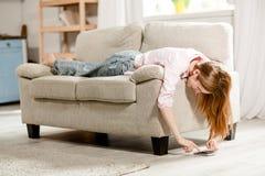Ung flicka som ligger på soffan som skriver på smartphonen Royaltyfri Fotografi