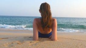 Ung flicka som ligger på stranden och att solbada för hav Oigenkännlig kvinna som kopplar av på havkust under lopp för sommarseme arkivfilmer
