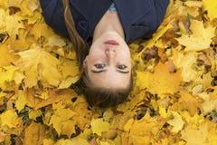 Ung flicka som ligger på stupade höstsidor Arkivbilder