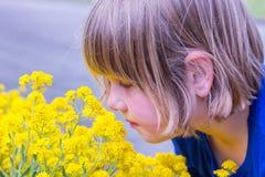 Ung flicka som luktar gulingblommor Arkivfoto