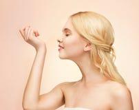 Ung flicka som luktar pefrume på hennes hand Fotografering för Bildbyråer