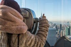Ung flicka som lurar till och med turist- kikare som reflekterar New York City Ung flicka som kikar till och med turist- kikare m Royaltyfria Bilder