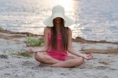 Ung flicka som mediterar på stranden Royaltyfria Foton