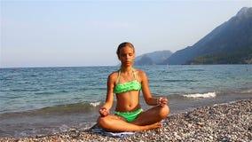 Ung flicka som mediterar på stranden stock video