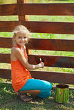 Ung flicka som målar ett trästaket Fotografering för Bildbyråer