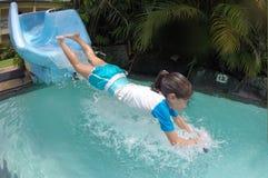 Ung flicka som plaskar in i pöl, når att ha gått ner vattenglidbana Royaltyfri Foto